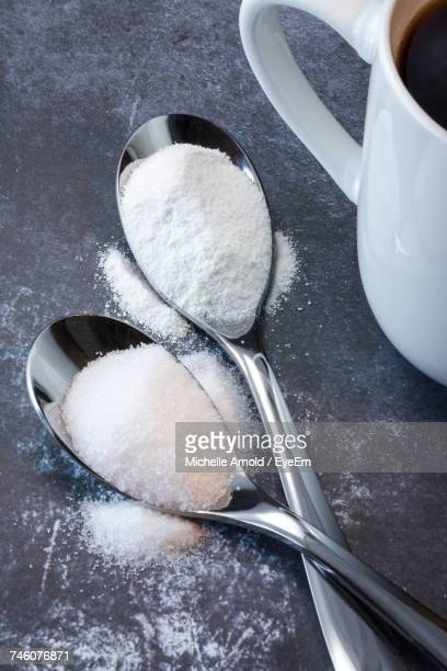 high angle view of creamer and sugar powders in spoons with black coffee cup on table - sugar coffee stock photos and pictures