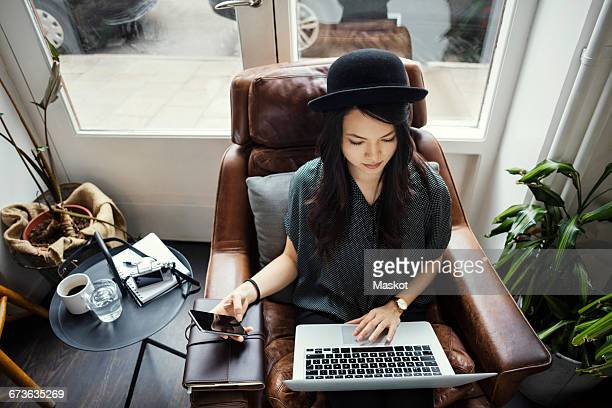 high angle view of creative businesswoman working while sitting on chair - blogging stock pictures, royalty-free photos & images