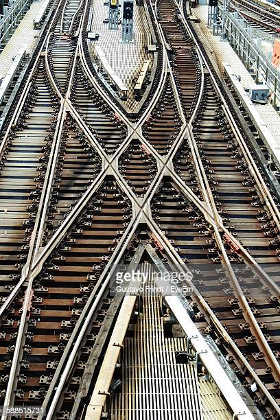 high angle view of crisscross railroad tracks at railway station - bahngleis stock-fotos und bilder