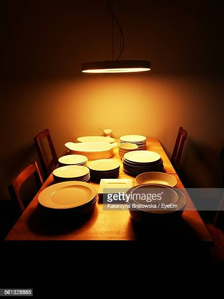 High Angle View Of Crockery Arranged On Illuminated Table At Home