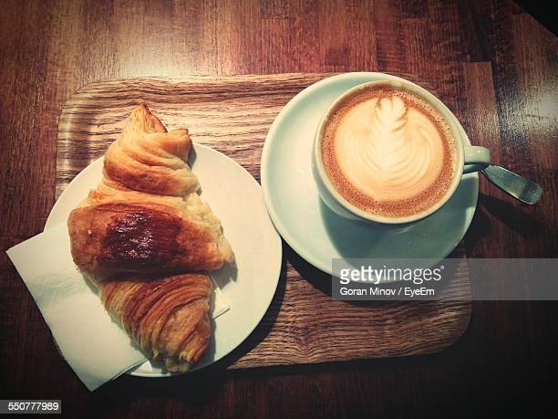 High Angle View Of Croissant And Coffee On Table