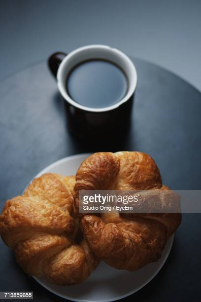 High Angle View Of Croissants With Coffee Cup On Table