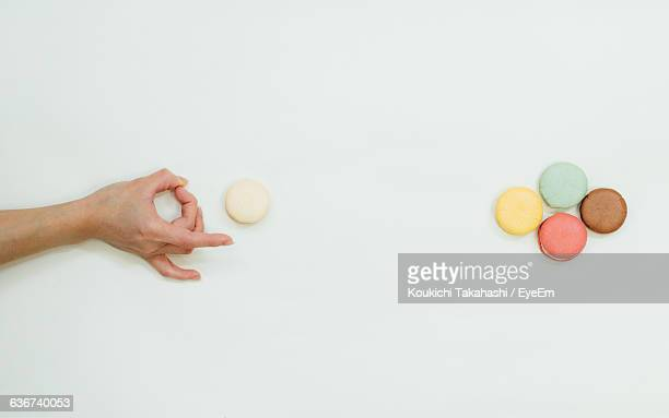 high angle view of cropped hand flipping macaroons on white background - lanciare foto e immagini stock