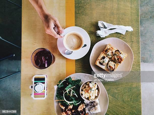 High Angle View Of Cropped Hand Holding Coffee Cup By Food Served On Table