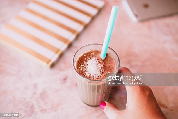 High Angle View Of Cropped Hand Holding Milk Shake Glass