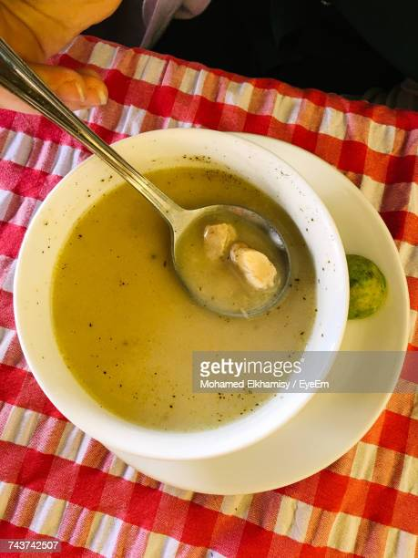 high angle view of cropped hand holding spoon over chicken soup bowl on table - chicken soup stock photos and pictures