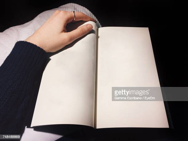 High Angle View Of Cropped Hand On Open Book With Blank Page At Table