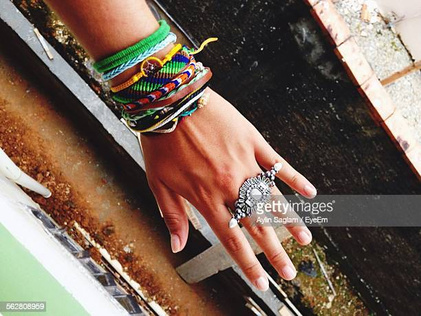 High Angle View Of Cropped Hand Wearing Bracelets And Ring