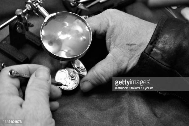 high angle view of cropped hands repairing pocket watch - broken arrow oklahoma stock photos and pictures