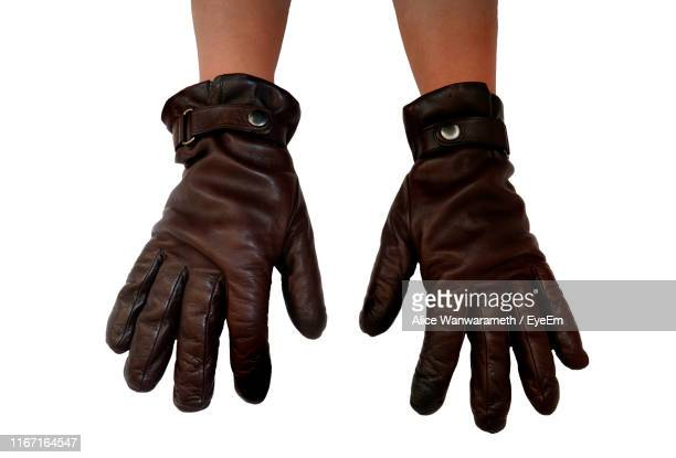 high angle view of cropped hands wearing brown leather gloves over white background - leather glove stock pictures, royalty-free photos & images