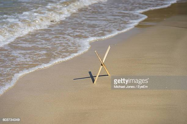 high angle view of cross shaped wood on sea shore - x marks the spot stock pictures, royalty-free photos & images