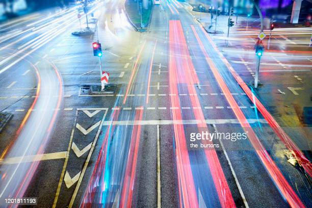 high angle view of crossroad and traffic lights with light trails of cars at night - verkehrswesen stock-fotos und bilder