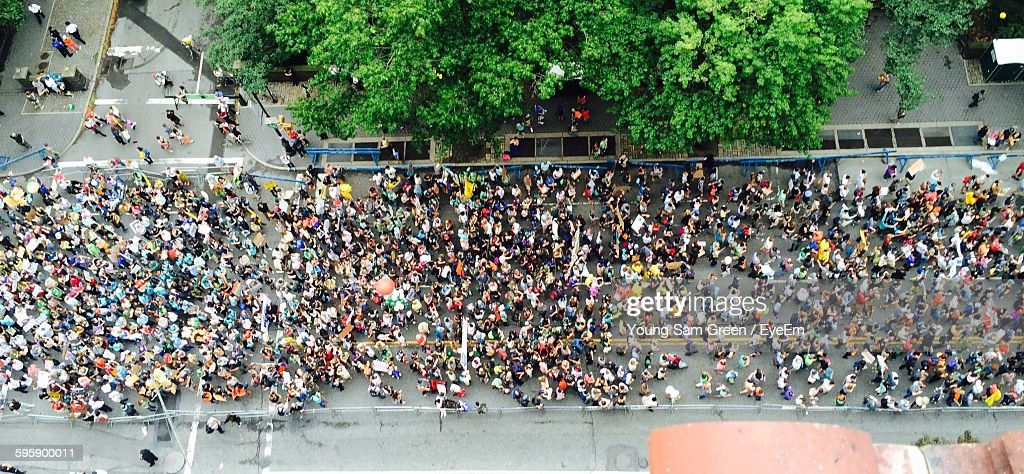 High Angle View Of Crowd Marching On Street By Tree : Stock Photo