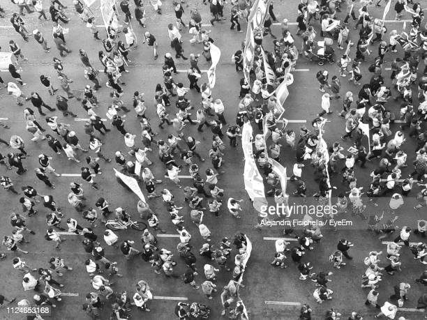high angle view of crowd on street - marsch stock-fotos und bilder