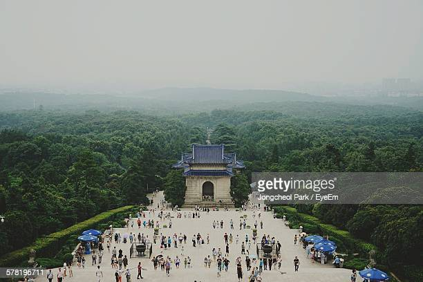 high angle view of crowd visiting sun yat-sen mausoleum surrounded by trees against sky - nanjing stock pictures, royalty-free photos & images
