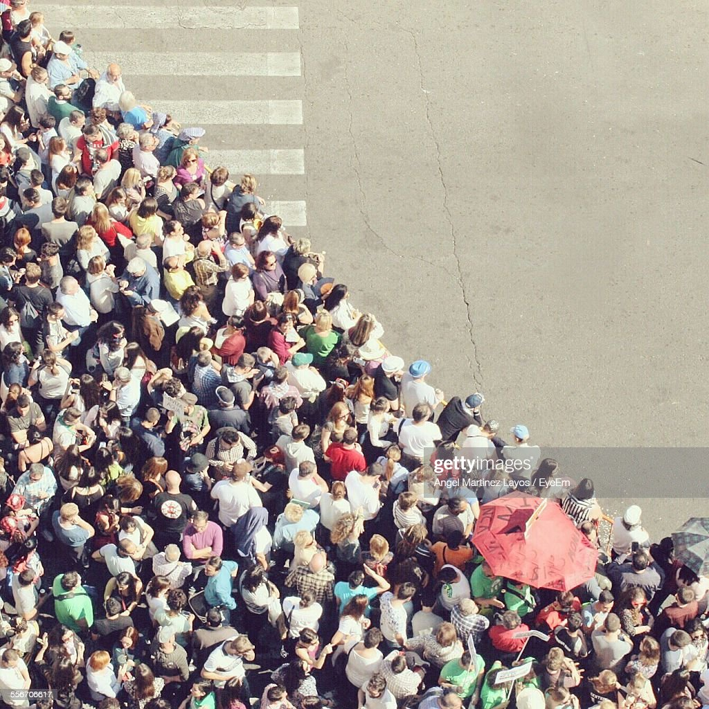 High Angle View Of Crowd Waiting At Crosswalk To Cross Road : Stock Photo
