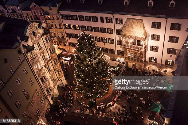 high angle view of crowds at christmas market at night, innsbruck, austria - innsbruck stock pictures, royalty-free photos & images