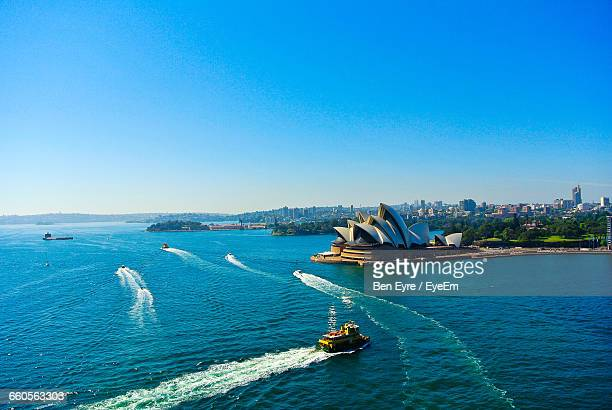 high angle view of cruise next to opera house against clear sky - sydney - fotografias e filmes do acervo