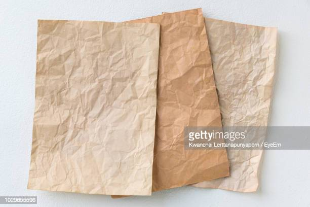 high angle view of crumpled paper against white background - kraft paper stock pictures, royalty-free photos & images