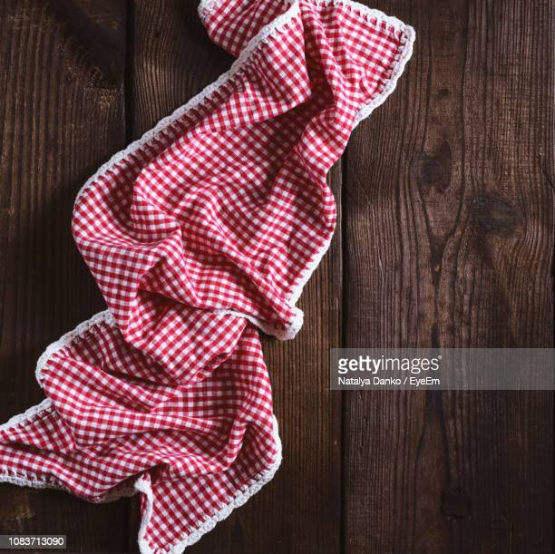 high angle view of crumpled red fabric on wooden table - dish towel stock pictures, royalty-free photos & images