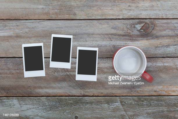 High Angle View Of Cup With Instant Transfer Prints On Wooden Table