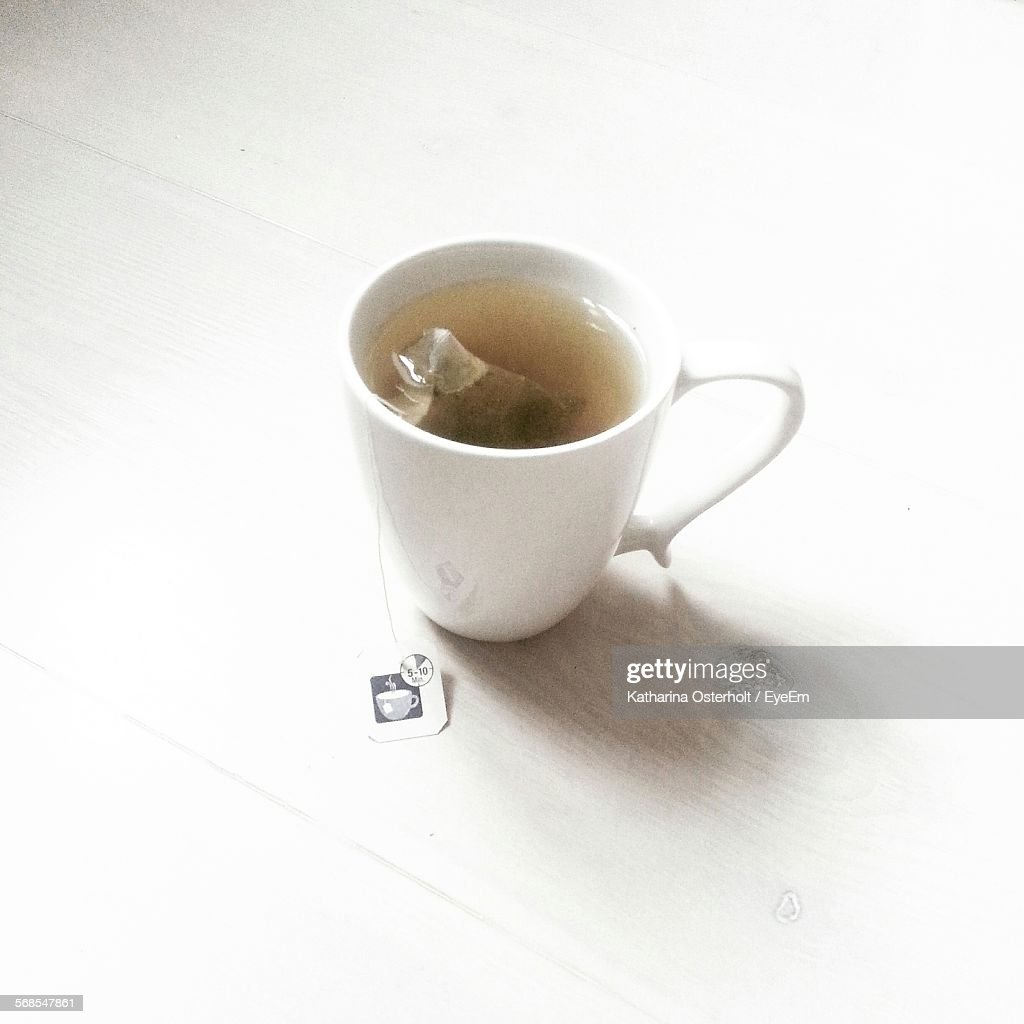 High Angle View Of Cup With Teabag On Table : Stock Photo