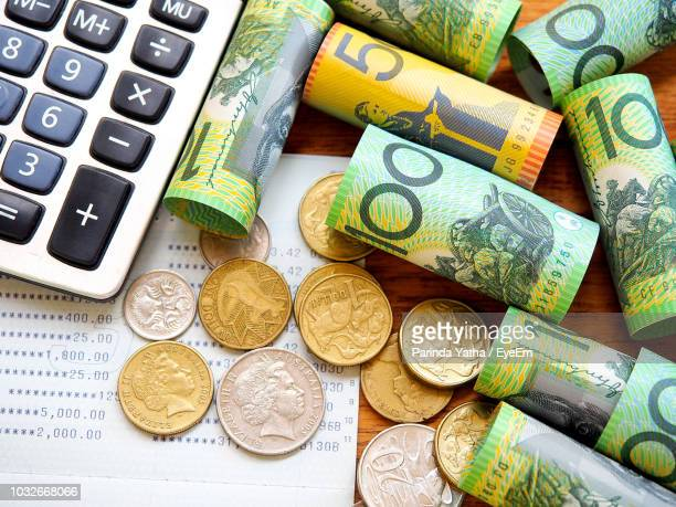 high angle view of currency and calculator on table - savings stock pictures, royalty-free photos & images