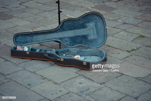 high angle view of currency in guitar case on footpath - guitar case stock pictures, royalty-free photos & images