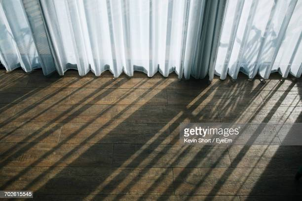 High Angle View Of Curtains Hanging At Window On Hardwood Floor