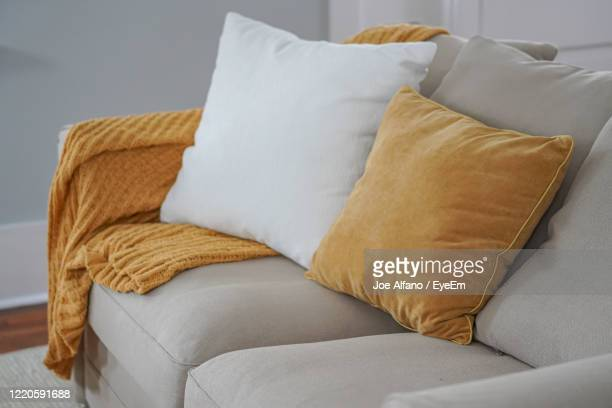 high angle view of cushions on sofa at home - cushion stock pictures, royalty-free photos & images