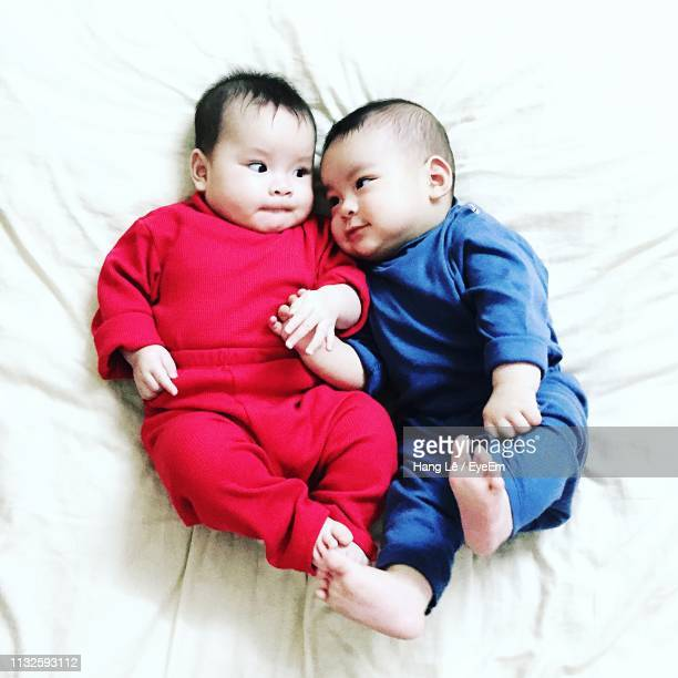 high angle view of cute babies lying on bed - 2 5 mesi foto e immagini stock