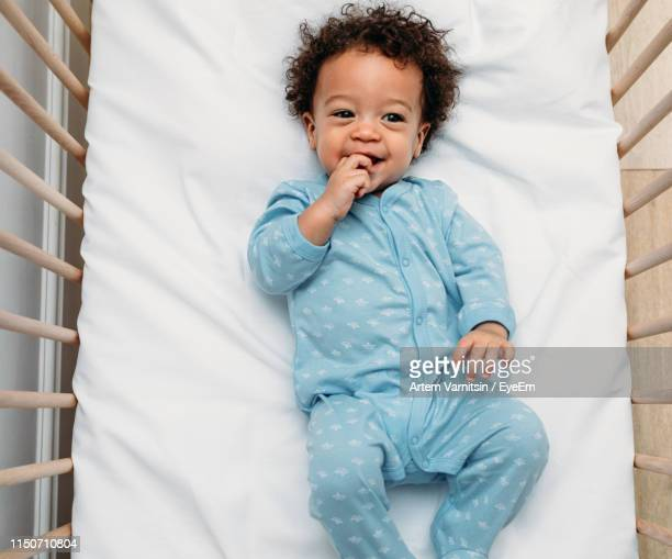 high angle view of cute baby boy lying in crib at home - baby boys stock pictures, royalty-free photos & images