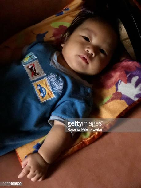 high angle view of cute baby boy lying on bed at home - rowena miller stock photos and pictures