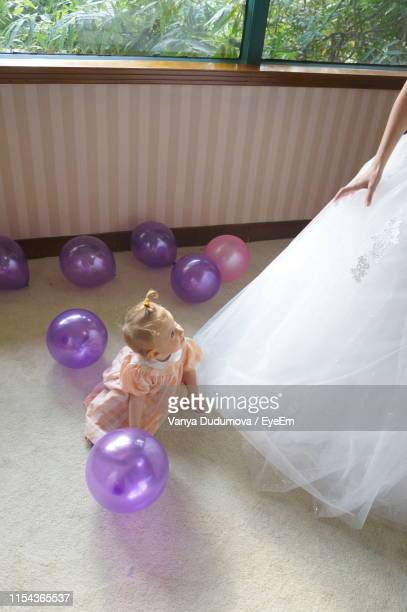 high angle view of cute baby girl sitting on floor looking at woman in wedding dress - wedding dress stock pictures, royalty-free photos & images