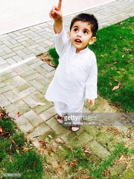 high angle view of cute boy pointing up while standing on footpath - cute pakistani boys stock photos and pictures