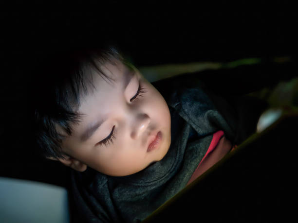 High Angle View Of Cute Boy Using Digital Tablet While Lying On Bed