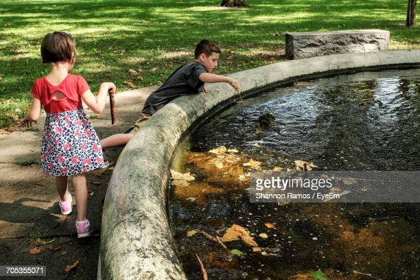 High Angle View Of Cute Brother And Sister Playing Near Pond In Park
