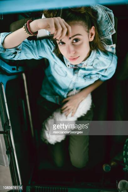 High Angle View Of Cute Female With Hair Buns Is Playing With Her Dog On A Front Seat