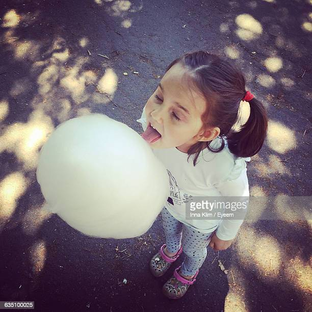 High Angle View Of Cute Girl Licking Candy Floss While Standing On Street