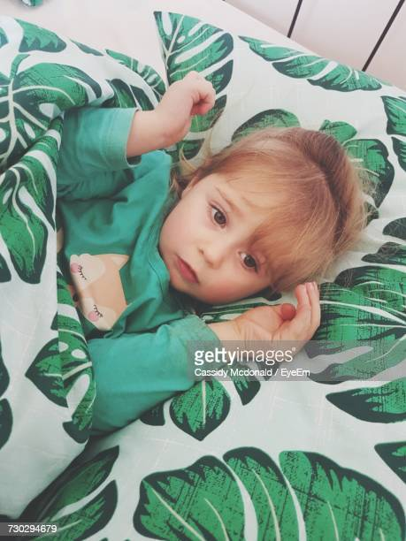 High Angle View Of Cute Girl Lying On Bed At Home
