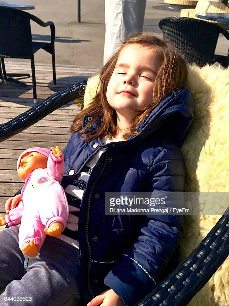 high angle view of cute girl with doll sleeping on chair - biljana doll stock photos and pictures