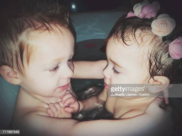 High Angle View Of Cute Naked Siblings Bathing In Wading Pool At Night
