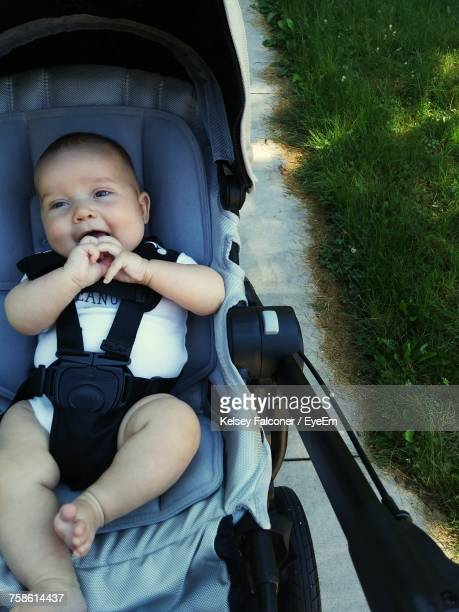 High Angle View Of Cute Toddler Sitting In Baby Carriage At Park