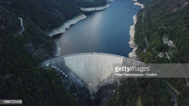 high angle view of dam amidst trees - energieindustrie stock-fotos und bilder