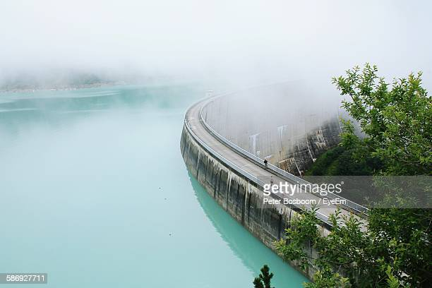 high angle view of dam by river during foggy weather - reservoir stock pictures, royalty-free photos & images