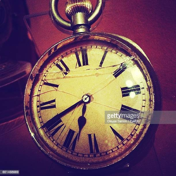 High Angle View Of Damaged Pocket Watch On Table