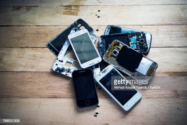 High Angle View Of Damaged Smart Phone On Wooden Table