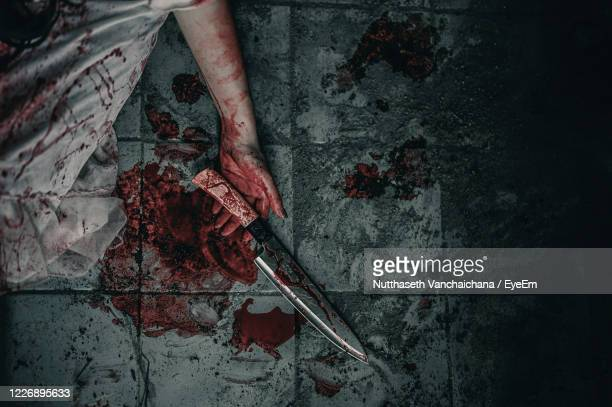 high angle view of dead woman with blood covered knife on floor - crime scene stock pictures, royalty-free photos & images