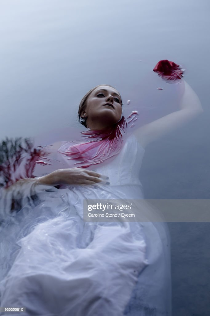 High Angle View Of Dead Young Woman Floating In Water : Stock Photo