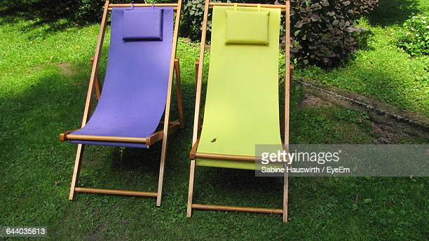 High Angle View Of Deck Chairs On Grassy Field